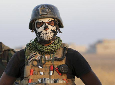 A member of Iraq's elite counterterrorism forces pauses as they advance towards the city of Mosul.