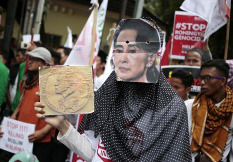 A woman wears a mask of Aung San Suu Kyi during a rally in Jakarta against the persecution of Rohingya. (Dita Alangkara; AP/PA)