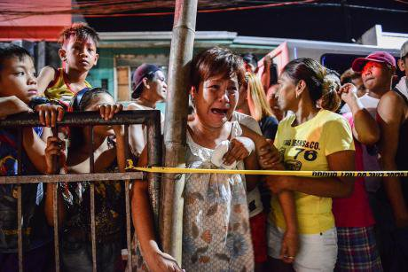 A woman cries near the body of a suspected drug user, shot dead north of Manila.