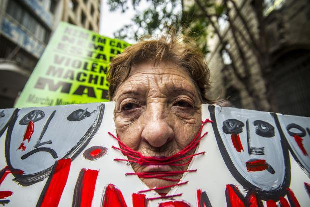 A woman with her head inside a protest banner at a demonstration in São Paulo against cuts to victims of violence against women