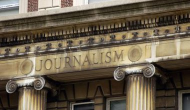 Pediment of neoclassical building with 'Journalism' carved into it.