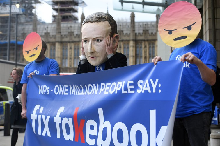 "Two people holding up a banner reading ""Fix Fakebook"", wearing masks of Facebook 'dislike' emojis, with someone wearing a Mark Zuckerberg mask behind the banner"