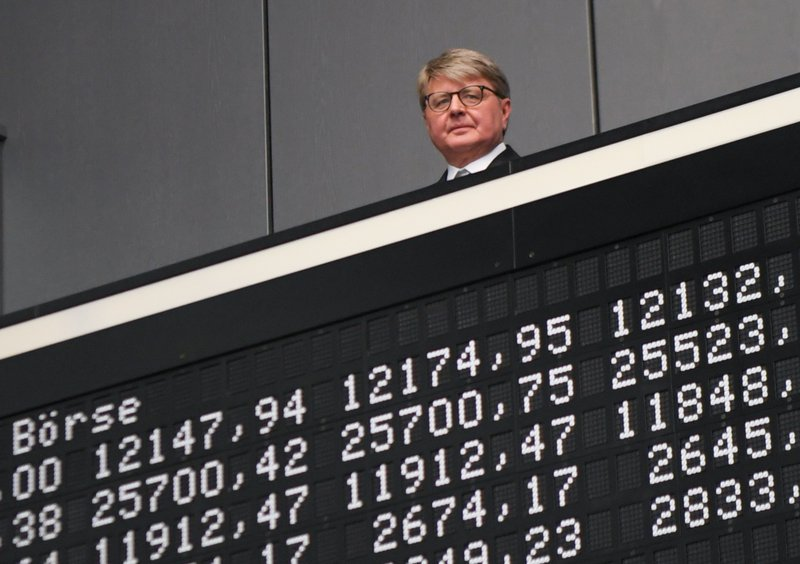 A man appearing above a stock exchange display board