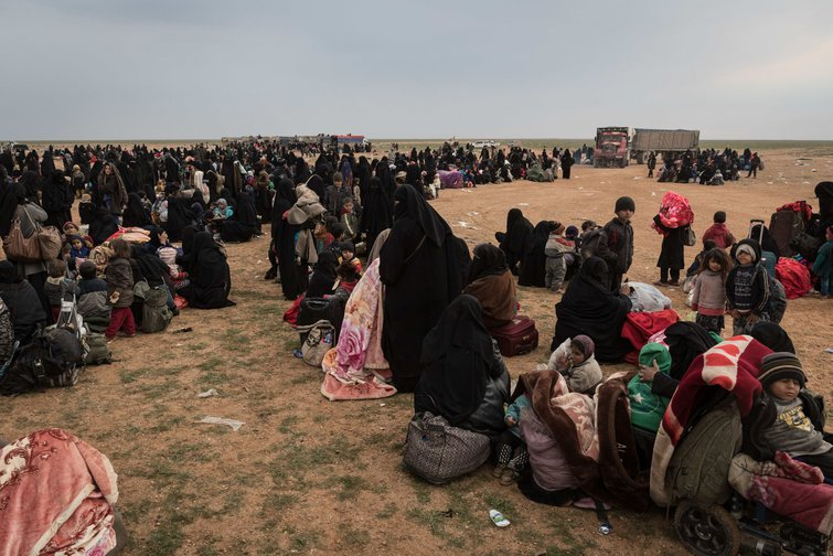 Women dressed in black with belongings gathered on a dry plain
