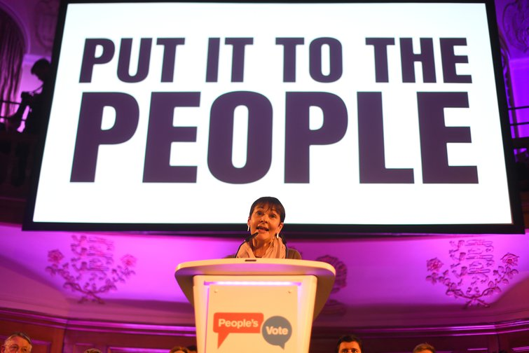 Caroline Lucas under a big sign reading 'Put it to the people'