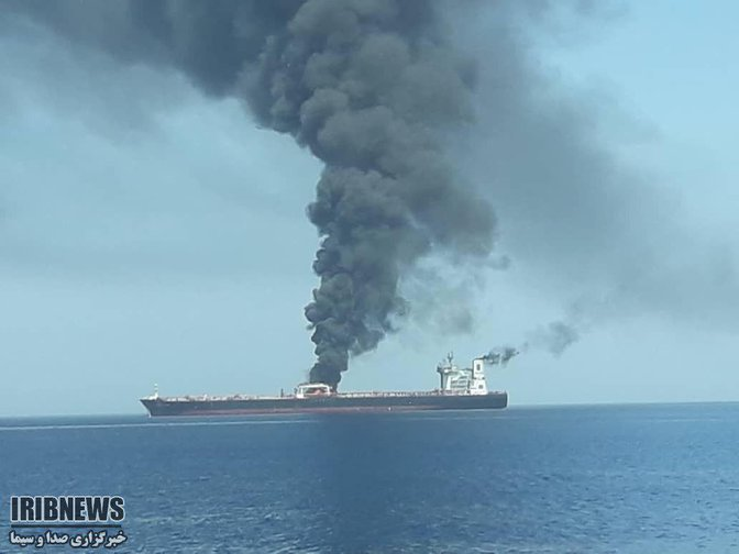 A large ship with a plume of black smoke rising from it