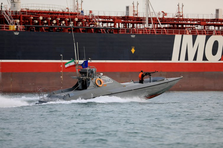 Speedboat with a gun mounted in the bows moving past an oil tanker