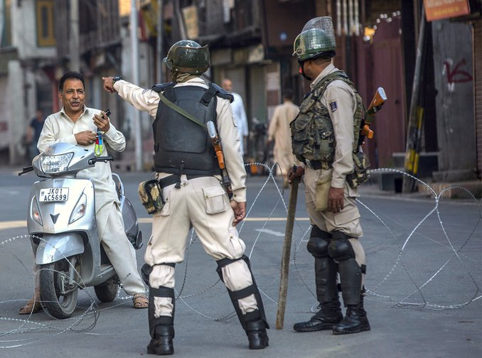 An Indian paramilitary trooper stops a man at a checkpoint in Srinagar, Kashmir.