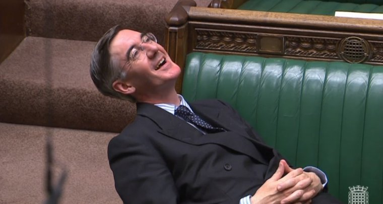 A man lying back on a green leather and carved wood bench, laughing, wearing glasses, a double-breasted suit and tie, with short back and sides