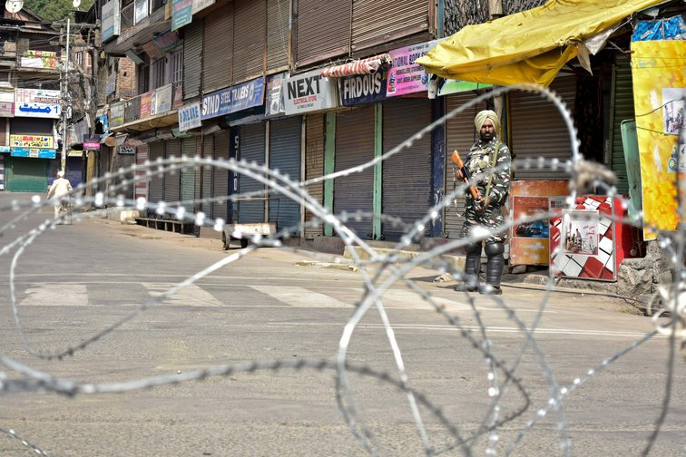 An Indian paramilitary trooper stands guard in Srinagar, Kashmir during the lockdown.