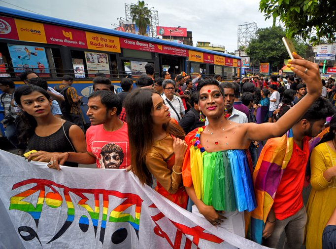 LGBTQ demonstration with rainbow Hindi text on a banner.