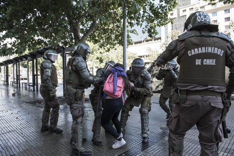 Riot police surrounding  and restraining someone with a pink backpack