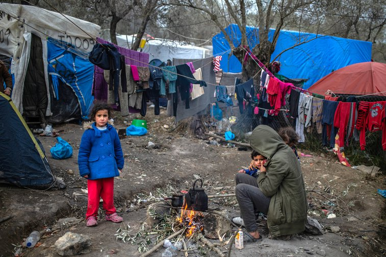Greece, Lesbos: A migrant family warming themselves by a small fire in a temporary camp next to the camp in Moria, 21 January 2020.