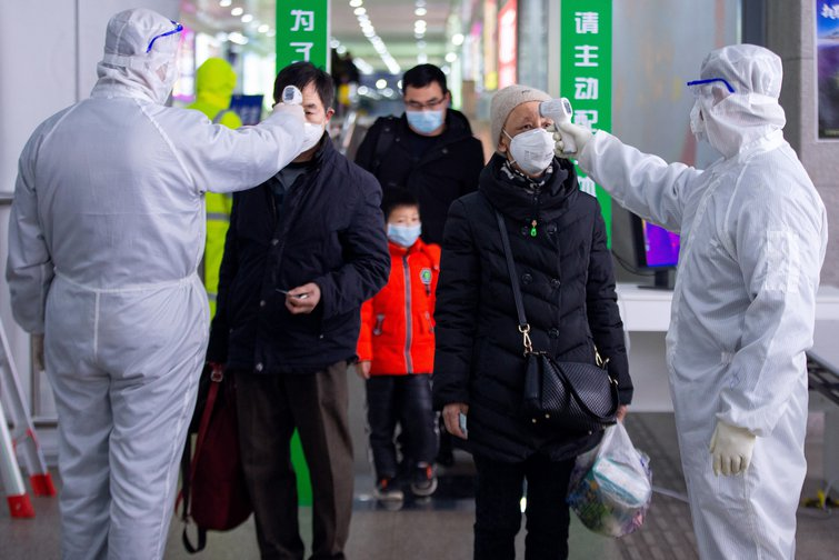 Chinese medical workers check passengers' body temperatures on arrival at Nanjing Railway Station, east China's Jiangsu Province, February 2020.