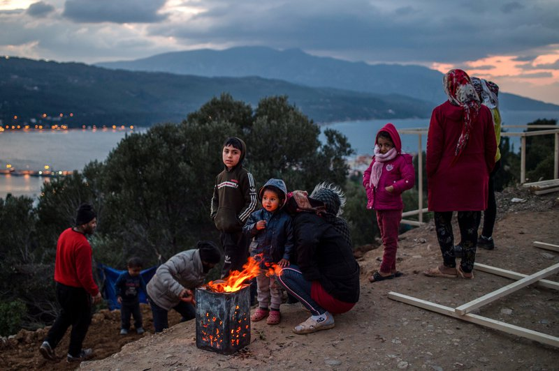 Refugees warm themselves by a campfire in a refugee camp on Samos, Greece.
