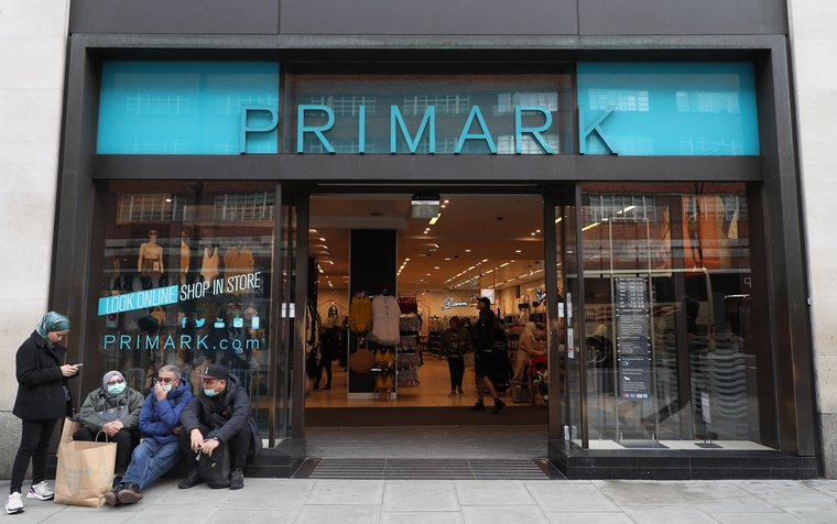 People in masks outside a Primark in Oxford Street in London, March 13, 2020.