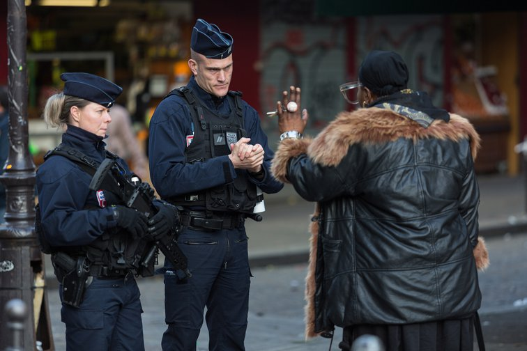 Two French police officers in Paris question a woman after the 6 p.m. curfew on March 17, 2020.