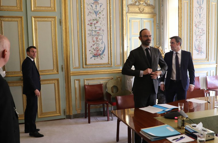 Emmanuel Macron, Edouard Philippe and Health Minister Olivier Veran leave the Elysee Palace after a call conference to install the CARE committee. March 24, 2020