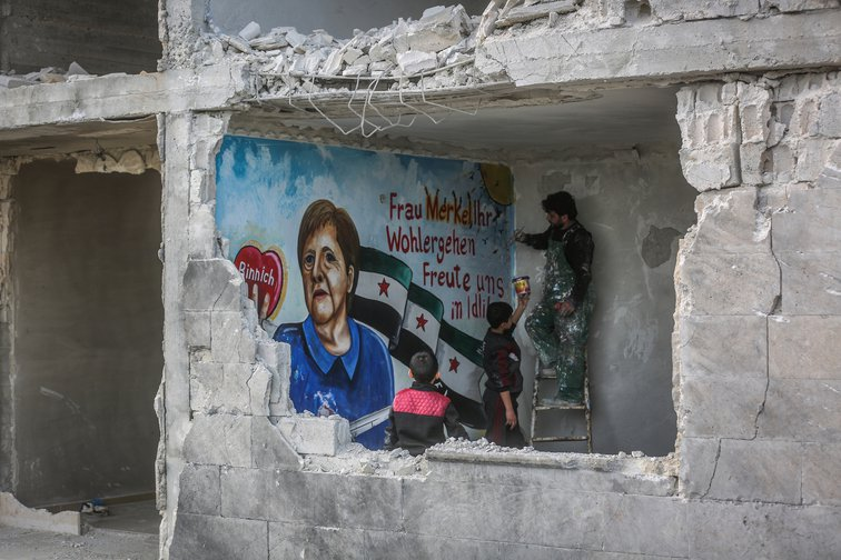 "Aziz Al-Asmar, a Syrian painter from Binnish, paints a mural, saying, ""Fra Merkel, we were happy once in Idlib"", March 26, 2020."