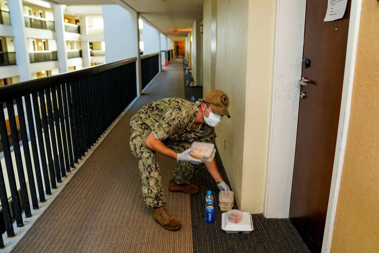 A U.S. Navy sailor delivers food to hotel rooms where sailors from the aircraft carrier USS Theodore Roosevelt who have tested negative for COVID-19 are quarantined April 3, 2020 in Tamuning, Guam.