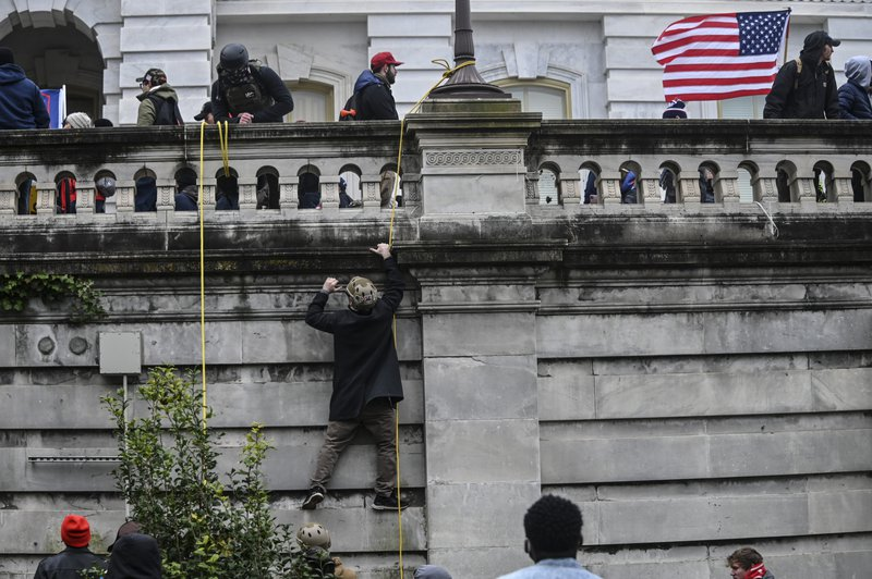 A Donald Trump supporter climbs the walls of the United States Capitol during the Trump inspired insurgency.