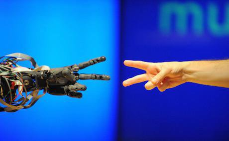 A robot faces off against a human in a game of 'rock paper scissors' at the Science Museum, London.