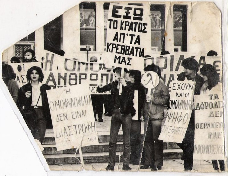 "Revenioti (centre) holds a placard that says ""(We want) the state out of our beds"" at a 1981 demonstration in Athens."