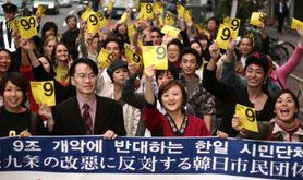 Crowd of young people behind a banner holding up yellow sheets with '9' written on them.