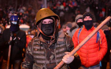 Militant protester on the Maidan with armour, a stick and helmet.