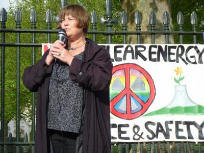 Women stands speaking, microphone in hands, next to a peace sign .