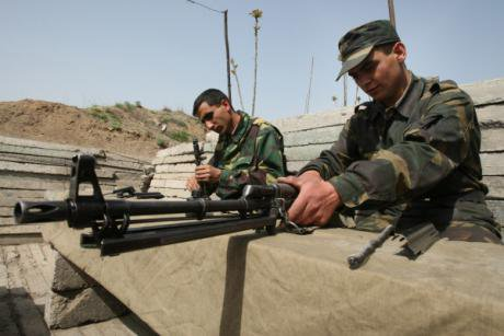 Nagorno-Karabakh troops clean their weapons in their trench on the 'line of contact'