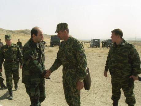 Two men in military uniform shake hands in a desert.