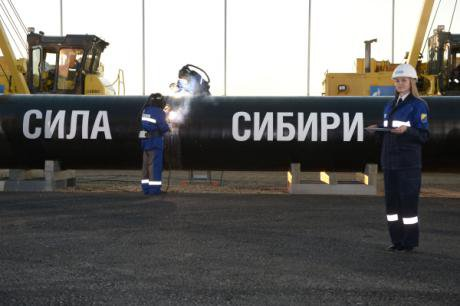 Russian workers stand in front of a piece of pipeline reading 'the power of Siberia.'