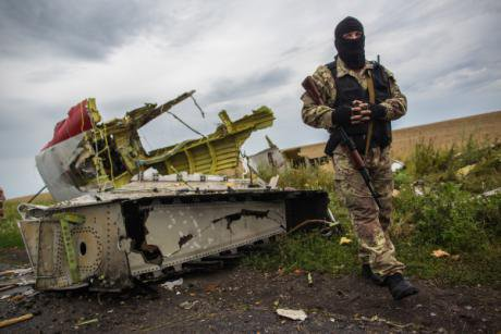 A rebel in a balaclava stands by a ruined piece of MH17.