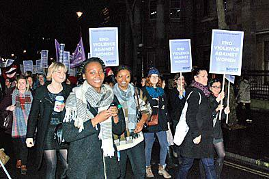 Women marching with placards in the dark