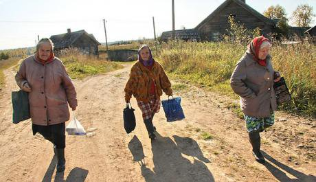 Three old Russian women walk down a dirt road in rural Russia carrying heavy bags.
