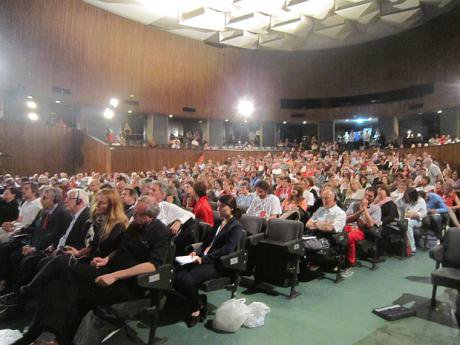 People seated in a full conference room.