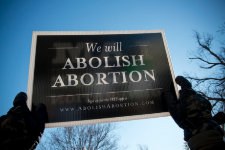 A protester holds an abolish abortion sign at a rally attended by young people in Washington DC, 22 January 2014.