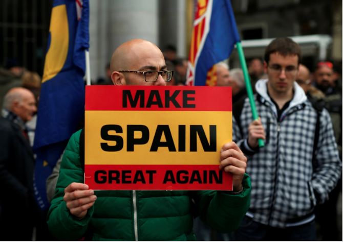 A man holds a 'Make Spain Great Again' sign at a gathering of supporters of Spain's former dictator Francisco Franco. | REUTERS/Javier Barbancho.