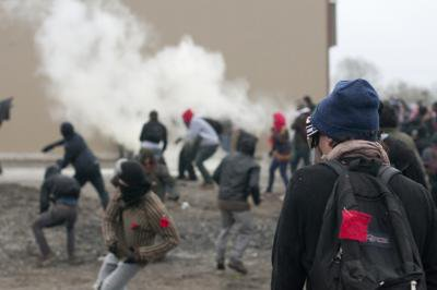 Students throw rocks at Surete du Quebec officers amidst tear gas during demo at Quebec Liberal Party Convention, 4 May 2012. Image Darren Ell..jpg