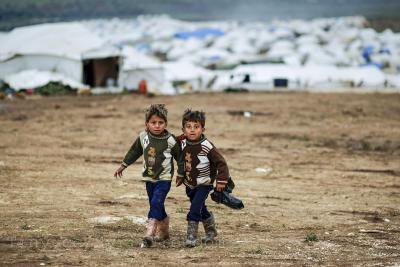 Syrian boys, whose family fled their home in Idlib, walk to their tent, at a camp for displaced Syrians, in the village of Atmeh, Syria, Monday, Dec. 10, 2012_0_0.jpg