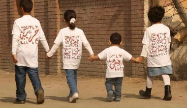 Four children holding hands walking away from the camera, wearing T-shirts with Arabic text on.