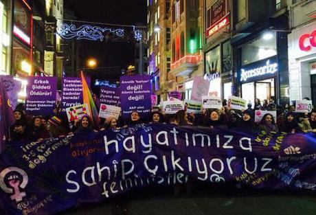 Women march at night with a banner