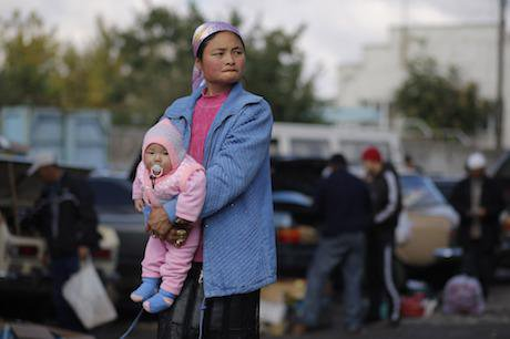A woman holds her baby at a street market in Tokmok, Kyrgyzstan. Credit: Alexander Zemlianichenko/AP/Press Association Images