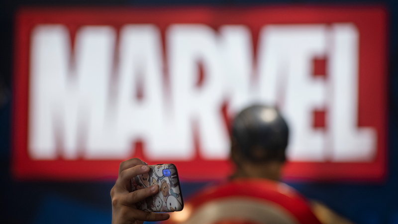 A visitor takes photos at Marvel Avengers movie character figures at Disney's Marvel Studio booth during the Ani-Com & Games event in Hong Kong.