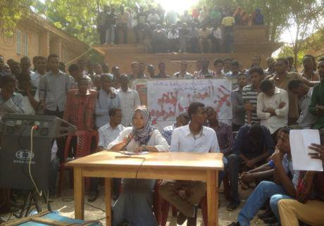 Male and Female student sit at a desk outside in front of a camera. Hundreds of student supporters  look on.