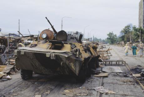 A burnt out armoured vehicle from the Abkhaz-Georgian War in 1994. Civilians walk by