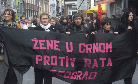 Women march holding a banner