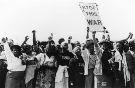 Women, arms raised, protesting. One with a sign 'Stop this war'.
