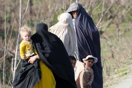 Heavily veiled women walk with their children in Swat valley, 2013.